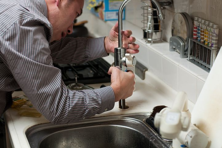 plumber working on a leaking faucet